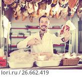 Купить «Seller offering displayed sorts of meat», фото № 26662419, снято 2 января 2017 г. (c) Яков Филимонов / Фотобанк Лори