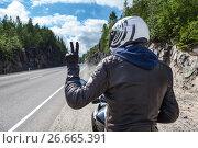 """Купить «Мотоциклист на мотоцикле на загородной трассе показывает знак """"победа"""" рукой в перчатках», фото № 26665391, снято 14 июля 2017 г. (c) Кекяляйнен Андрей / Фотобанк Лори"""