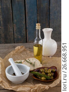 Купить «High angle view of olives with oil bottle and bread by spices in mortar pestle on table», фото № 26668951, снято 15 февраля 2017 г. (c) Wavebreak Media / Фотобанк Лори