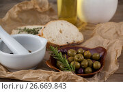 Купить «Mortar pestle by olives in plate on paper», фото № 26669843, снято 15 февраля 2017 г. (c) Wavebreak Media / Фотобанк Лори