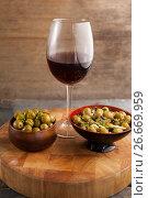 Купить «High angle view of olives served in bowls by wineglass on table», фото № 26669959, снято 15 февраля 2017 г. (c) Wavebreak Media / Фотобанк Лори