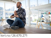 Купить «Male executive performing yoga on a table», фото № 26670271, снято 26 марта 2017 г. (c) Wavebreak Media / Фотобанк Лори