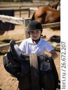 Smiling girl holding horse saddle in the ranch. Стоковое фото, агентство Wavebreak Media / Фотобанк Лори
