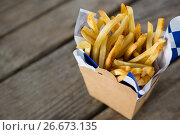 Купить «French fries with wax paper in container», фото № 26673135, снято 13 января 2017 г. (c) Wavebreak Media / Фотобанк Лори