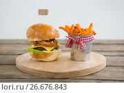 Купить «Hamburger by french fries in container on cutting board», фото № 26676843, снято 13 января 2017 г. (c) Wavebreak Media / Фотобанк Лори
