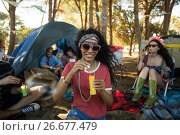 Smiling young woman holding bubble wand at campsite. Стоковое фото, агентство Wavebreak Media / Фотобанк Лори