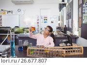 Купить «Elementary student examining liquid in beaker», фото № 26677807, снято 11 марта 2017 г. (c) Wavebreak Media / Фотобанк Лори