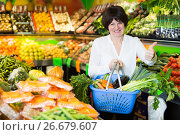 Купить «Middle aged woman with basket choosing vegetables», фото № 26679607, снято 10 марта 2017 г. (c) Яков Филимонов / Фотобанк Лори
