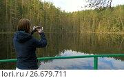 Купить «Girl make a picture using phone in the forest», видеоролик № 26679711, снято 17 мая 2017 г. (c) Dzmitry Astapkovich / Фотобанк Лори