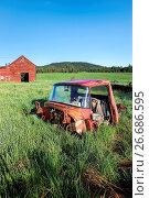 Купить «The torn up cab of an old truck in the grass near a red barn south of Tensed, Idaho.», фото № 26686595, снято 18 января 2019 г. (c) easy Fotostock / Фотобанк Лори