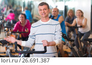 Купить «Elderly man on fitness cycle in fitness club», фото № 26691387, снято 15 декабря 2018 г. (c) Яков Филимонов / Фотобанк Лори