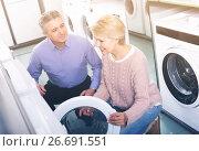 Купить «mature couple chooses washing machine for their house in shop of household appliances», фото № 26691551, снято 27 марта 2019 г. (c) Яков Филимонов / Фотобанк Лори