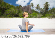 Купить «woman doing yoga in twist pose on beach», фото № 26692799, снято 13 ноября 2015 г. (c) Syda Productions / Фотобанк Лори