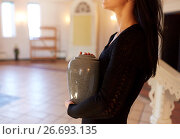 Купить «close up of woman with cremation urn in church», фото № 26693135, снято 20 марта 2017 г. (c) Syda Productions / Фотобанк Лори