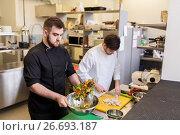 Купить «chef and cook cooking food at restaurant kitchen», фото № 26693187, снято 2 апреля 2017 г. (c) Syda Productions / Фотобанк Лори