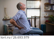 Side view of senior male patient suffering from back ache while looking up on bed. Стоковое фото, агентство Wavebreak Media / Фотобанк Лори