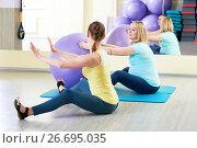 Купить «pregnant woman doing fitness ball exercise with coach», фото № 26695035, снято 3 марта 2017 г. (c) Дмитрий Калиновский / Фотобанк Лори