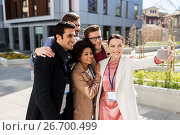 Купить «happy people with conference badges taking selfie», фото № 26700499, снято 13 мая 2017 г. (c) Syda Productions / Фотобанк Лори