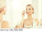 Купить «young woman with lotion washing face at bathroom», фото № 26700559, снято 13 февраля 2016 г. (c) Syda Productions / Фотобанк Лори