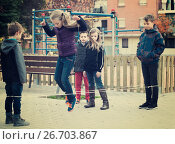 Купить «Kids skipping on chinese jumping elastic rope in yard», фото № 26703867, снято 14 декабря 2017 г. (c) Яков Филимонов / Фотобанк Лори