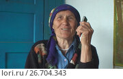 The elderly woman in a colorful headscarf talking on the phone. Стоковое видео, видеограф Gennadij Eichhorn / Фотобанк Лори