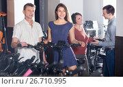 Купить «Employee helping family select bikes», фото № 26710995, снято 16 октября 2018 г. (c) Яков Филимонов / Фотобанк Лори
