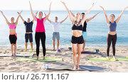 Купить «People practicing yoga on beach», фото № 26711167, снято 14 июня 2017 г. (c) Яков Филимонов / Фотобанк Лори