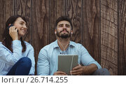 Купить «Composite image of man listening music with headphone while woman is using her mobile phone», фото № 26714255, снято 23 марта 2019 г. (c) Wavebreak Media / Фотобанк Лори