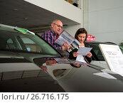 Посетители автосалона изучают прайс листы на новые машины (2017 год). Редакционное фото, фотограф Вячеслав Палес / Фотобанк Лори