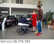 Купить «Молодая семья с коляской в автосалоне», фото № 26716183, снято 4 июня 2017 г. (c) Вячеслав Палес / Фотобанк Лори