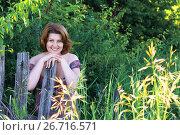 Купить «woman in dress with open shoulders stands near the fence», фото № 26716571, снято 21 июня 2017 г. (c) Володина Ольга / Фотобанк Лори
