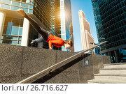 Купить «Young girl doing yoga outdoors in city», фото № 26716627, снято 3 октября 2015 г. (c) Сергей Тимофеев / Фотобанк Лори