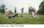 Three young sportsmen practice yoga in the park. Стоковое видео, видеограф Константин Шишкин / Фотобанк Лори