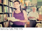 Купить «Smiling young female is looking new novel in shop», фото № 26718115, снято 28 июня 2017 г. (c) Яков Филимонов / Фотобанк Лори