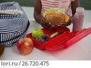 Купить «Schoolgirl having sandwich», фото № 26720475, снято 5 апреля 2017 г. (c) Wavebreak Media / Фотобанк Лори