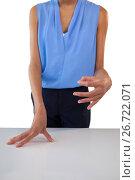 Купить «Businesswoman holding something while gesturing at table», фото № 26722071, снято 19 января 2017 г. (c) Wavebreak Media / Фотобанк Лори