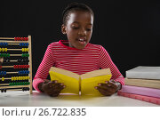 Купить «Schoolgirl reading a book against black background», фото № 26722835, снято 5 апреля 2017 г. (c) Wavebreak Media / Фотобанк Лори