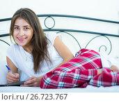 Купить «Smiling girl making shopping list in bedroom», фото № 26723767, снято 23 февраля 2019 г. (c) Яков Филимонов / Фотобанк Лори