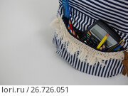 Купить «Schoolbag with various supplies on white background», фото № 26726051, снято 5 апреля 2017 г. (c) Wavebreak Media / Фотобанк Лори