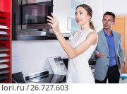 Купить «Couple is choosing new microwave», фото № 26727603, снято 15 июня 2017 г. (c) Яков Филимонов / Фотобанк Лори