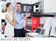 Купить «Happy family couple choosing new microwave», фото № 26727615, снято 15 июня 2017 г. (c) Яков Филимонов / Фотобанк Лори