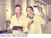 Купить «Man and woman employees on winery manufactory», фото № 26727635, снято 20 августа 2018 г. (c) Яков Филимонов / Фотобанк Лори