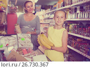 Купить «girl and mom are standing near trolley with groceries», фото № 26730367, снято 5 июня 2017 г. (c) Яков Филимонов / Фотобанк Лори