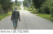 Купить «Old woman walking on the road at the sunny day», видеоролик № 26732643, снято 25 июля 2017 г. (c) worker / Фотобанк Лори