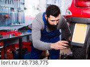 Купить «Man worker fixing failed scooter in workshop», фото № 26738775, снято 25 сентября 2018 г. (c) Яков Филимонов / Фотобанк Лори