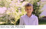 Купить «smiling preteen boy outdoors at summer garden», видеоролик № 26753023, снято 28 февраля 2020 г. (c) Syda Productions / Фотобанк Лори
