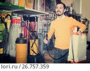 Купить «Positive guy deciding on best garden sprayer», фото № 26757359, снято 2 марта 2017 г. (c) Яков Филимонов / Фотобанк Лори