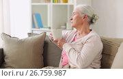 Купить «senior woman with cup of tea or coffee at home», видеоролик № 26759987, снято 7 апреля 2020 г. (c) Syda Productions / Фотобанк Лори