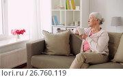 Купить «senior woman with cup of tea or coffee at home», видеоролик № 26760119, снято 25 июня 2017 г. (c) Syda Productions / Фотобанк Лори