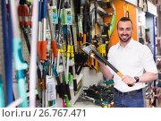 Купить «Man selecting axe in household store», фото № 26767471, снято 17 июля 2018 г. (c) Яков Филимонов / Фотобанк Лори